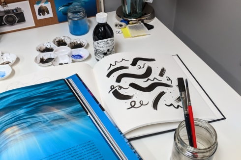 Desk and sketches with inspiration book