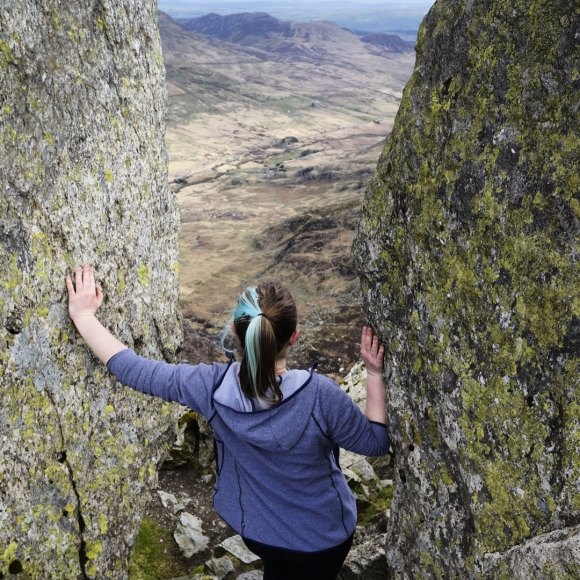 Jem standing at the top of Tryfan in North Wales, between the standing stones