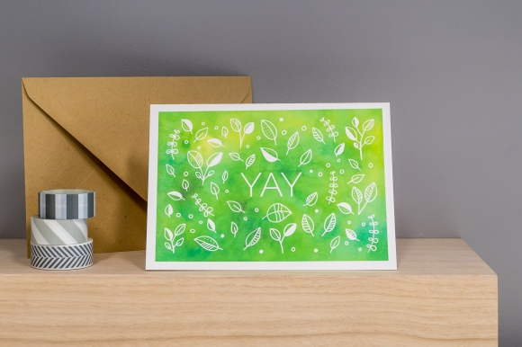 Product photograph showing my Yay greetings card design on a wooden shelf