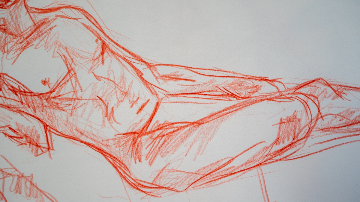 Close up of a life drawing sketch by Jem, showing a reclining male figure drawn in red pencil