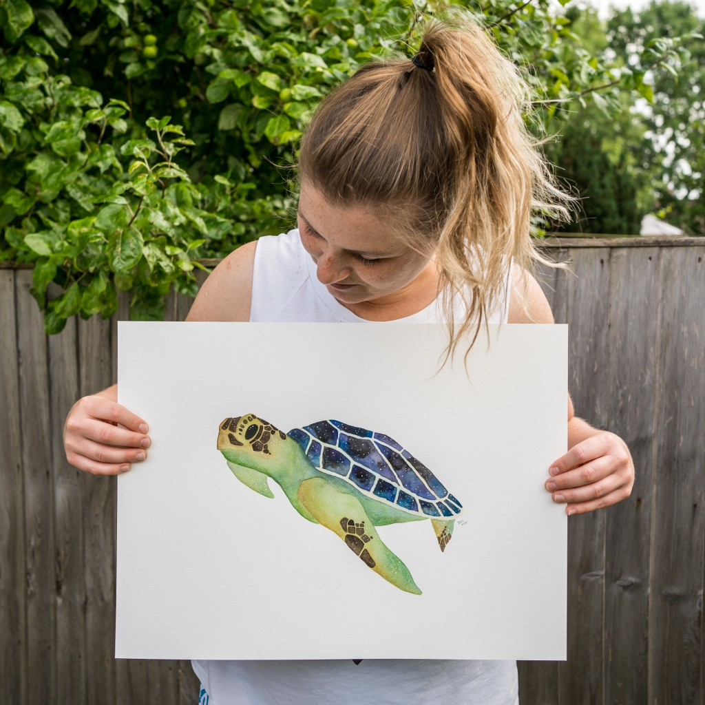 Jem in her garden holding up her finished sea turtle painting