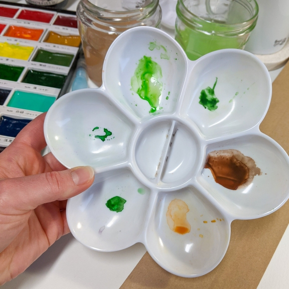 Jem holding a paint palette in her home studio, showing the vibrant greens and earthy browns used to paint the Earth collection