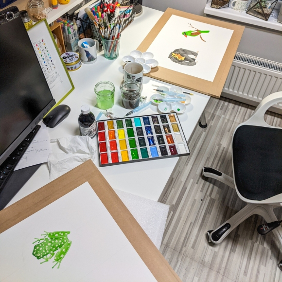 Jem's desk in her home studio, showing all three paintings from the Earth collection in progress surrounded by watercolour paints and art materials
