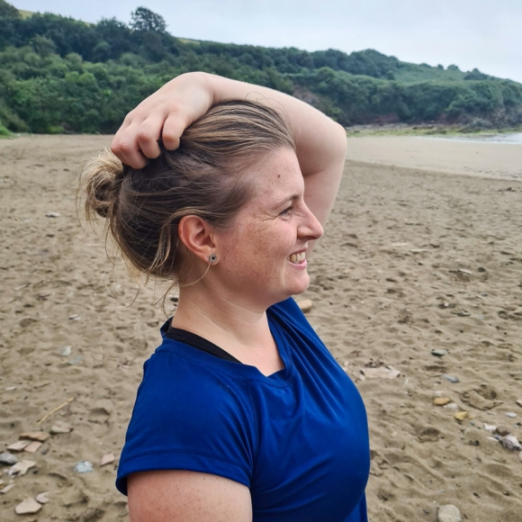 Side-on portrait of Jem standing on a beach in South Devon, looking out to sea and smiling