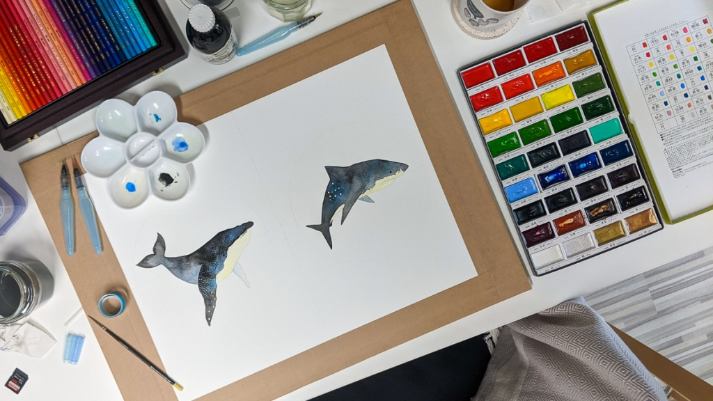 Flatlay showing Jem's humpback whale and tiger shark paintings in progress, surrounded by paint and paintbrushes